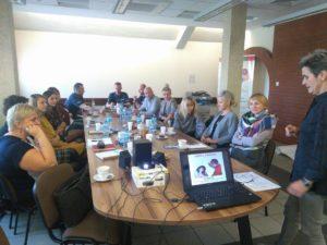 Na zdjęciu widać 13 osób, które siedzą przy stole konferencyjnym isłuchają osoby prowadzącej szkolenie. Osoba prowadząca szkolenie stoi przy stole ipatrzy nalaptop, naktórym wyświetlona jest treść szkolenia.
