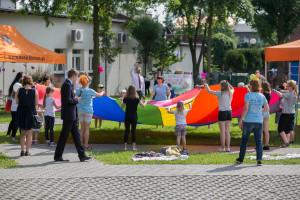 Uczestnicy spotkania wtrakcie zabawy zchustą Klanza. Dorośli idzieci trzymają wkoło chustę ipodrzucają nią piłeczki dogóry